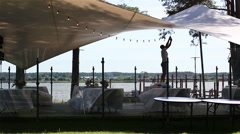 Man arranging light bubbles garland at a summer terrace near the lake Stock Footage