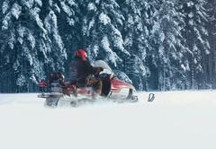 Stock Photo of Driver man riding on a snowmobile through the snow in a snowy forest trees