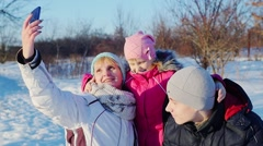Woman do selfie with two children in the winter park Stock Footage