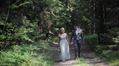 Young and happy bride and groom walking in the sunny forest - stock footage