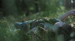 Young woman in the forest lying on the moss and touching the plants around her - stock footage