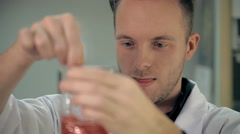 The laboratorian is mixing the ingredients in a glass Stock Footage