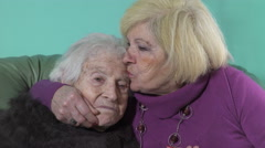 Stock Video Footage of Old woman with an expressive face hugged and kissed by her mature daughter