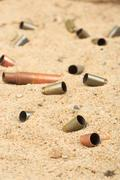 Cartridge cases on the sand Stock Photos