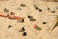 cartridge cases on the sand - stock photo