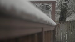 Snow collects on a fence as a man walks past Stock Footage