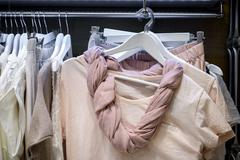 Dresses on hangers in wardrobe Stock Photos