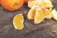 Stock Photo of Fresh ripe sweet orange tropical fruit on wooden table.