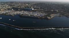 Orbiting left to right above harbor and jetty at Redondo Beach, California. Shot Stock Footage