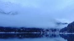 Sunset on an alpine lake Ritsa winter under gloomy clouds, Abkhazia. Full HD Stock Footage