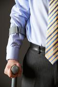 Close Up Of Businessman Using Crutch - stock photo