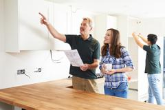 Woman With Carpenter Looking At Plans For New Kitchen - stock photo