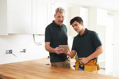 Carpenter And Apprentice With Digital Tablet Fitting Luxury Kitchen Stock Photos