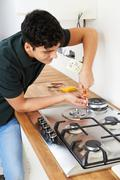 Workman Installing Gas Cooker In New Kitchen Stock Photos