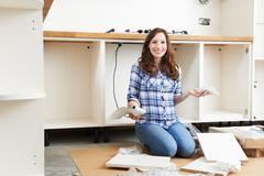 Woman With Self Assembly Furniture In Kitchen - stock photo