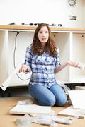 Frustrated Woman With Self Assembly Furniture In Kitchen - stock photo