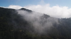 Flying through clouds over the Angeles National Forest on the slopes of the San Stock Footage