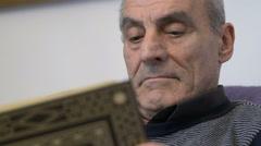 Adult man reading a book, hardcopy, grey hair Stock Footage