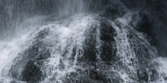 Water pouring down onto a stream cascading over dark boulders Stock Footage