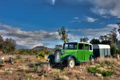 Old car and trailer with Highway 33 in background. - stock photo