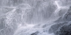 Stream cascading over dark boulders viewed through heavy curtain of falling - stock footage