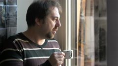 White man looks trough the window sipping a cup of tea Stock Footage