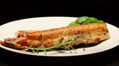 Smoked carp with aromatic herbs on white plate, rotating - stock footage