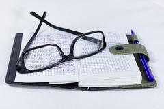 Glasses notebook and pen on the table - stock photo