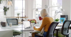 Young business woman drinking coffee working at shared workspace desk in trendy Stock Footage