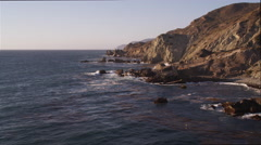 Over splashing surf and rock formations on the Catalina coast, pelicans flapping Stock Footage