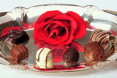 Chocolates and red rose on a sliver platter. Stock Photos