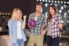 Cheerful young friends are entertaining in kegling club Stock Photos