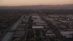 Flying over the outskirts of Los Angeles at dusk, downtown skyscrapers in Stock Footage