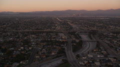 Flying over Los Angeles freeways and interchanges toward downtown in evening Stock Footage