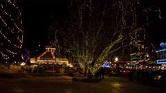 Right pan over a park beside a village street decorated with Christmas lights Stock Footage