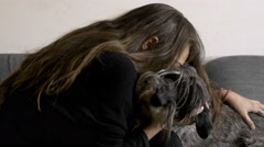 Woman plays with her dog in the living room, friendship - stock footage