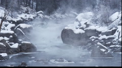 Mists rising from a freezing river flowing in a narrow channel between Stock Footage
