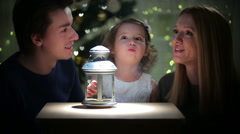 Cute little girl lights the magic lantern with their parents. Stock Footage