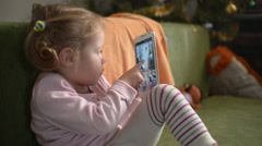 Little Girl touching A Screen Of Mobile Phone sitting On A Sofa Stock Footage
