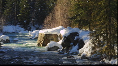 Sunlight on a freezing forest stream between snow-covered rocky banks Stock Footage