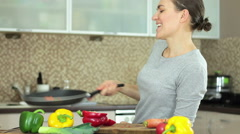 Young woman cook throwing vegetables in the air with a frying pan HD Stock Footage
