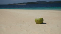 Coconut with drinking straw on the sand at the sea Stock Footage