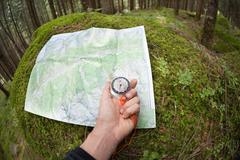 finding the right position in the forest with a map and compass - stock photo