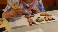 Woman is Painting a Cookie With Yellow Mastique Woman is Decorating a Christmas - stock footage