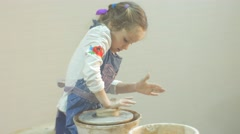 Girl is Pressing a Clay Panorama of a Workshop Working on a Pottery Wheel Stock Footage