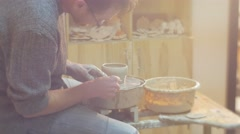 Man is Molding a Clay Pot by Stick Raw Pot Rotating Man Working on a Pottery Stock Footage