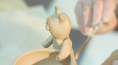 Male Hands Glue a Tail to a Clay Cat Statuette Fixed to a Pot Man is Putting a Stock Footage