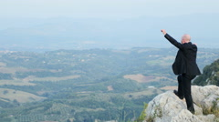 Businessman on a mountain peak, rock, valley Stock Footage