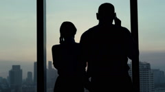 Silhouette of young business couple talking on cellphone in office during sunset Stock Footage