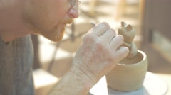 Man is Covering a Clay Pot and Cat Statuette Fixed to a Pot Cover with Water Stock Footage
